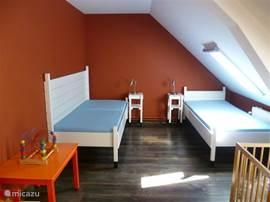Slaapkamer op de eerste verdieping voorzien van twee eenpersoonsbedden en een kinderledikant