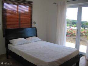 Hoofdslaapkamer met eigen badkamer en openslaande deuren naar terrasje. Ruime kledingkast en airconditioning.