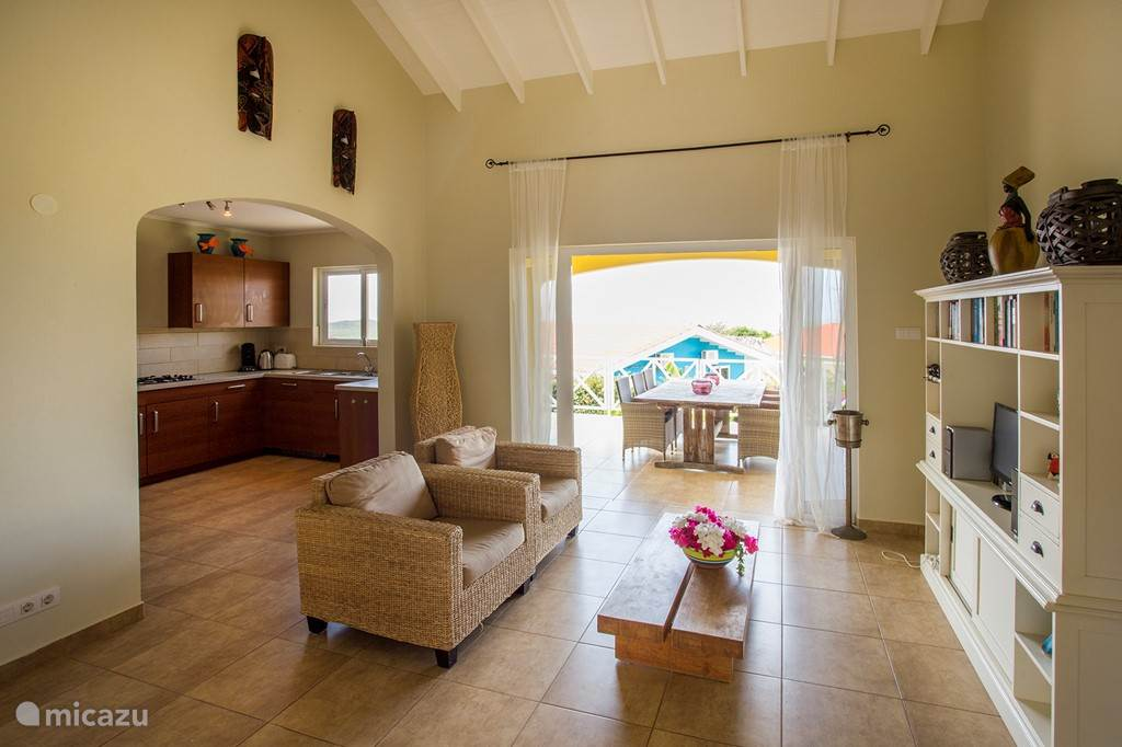Fijne, sfeervolle woonkamer met open keuken en toegang tot het terras.
