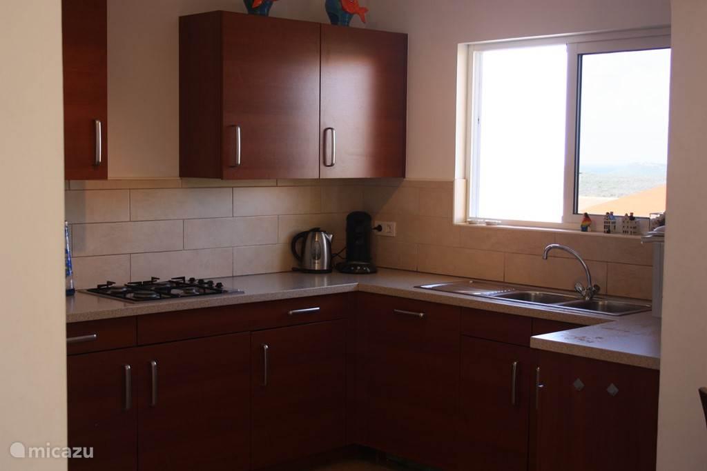 Luxe keuken met onder andere vaatwasser en warm water.