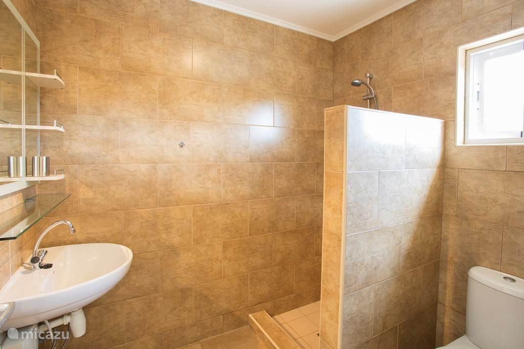 Ruime badkamer met grote douche, wastafel en toilet. Gelegen tussen slaapkamer 2 en 3. Warm (door middel van heater) en koud stromend water.