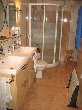 Part of the bathroom with sink, toilet and shower. In the room there is also a bathtub.