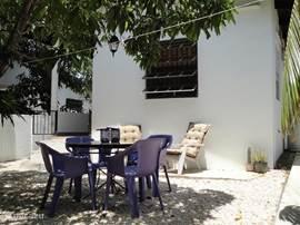 Buiten zit u heerlijk in de schaduw van de mangobomen en de verkoeling van de passaatwind.