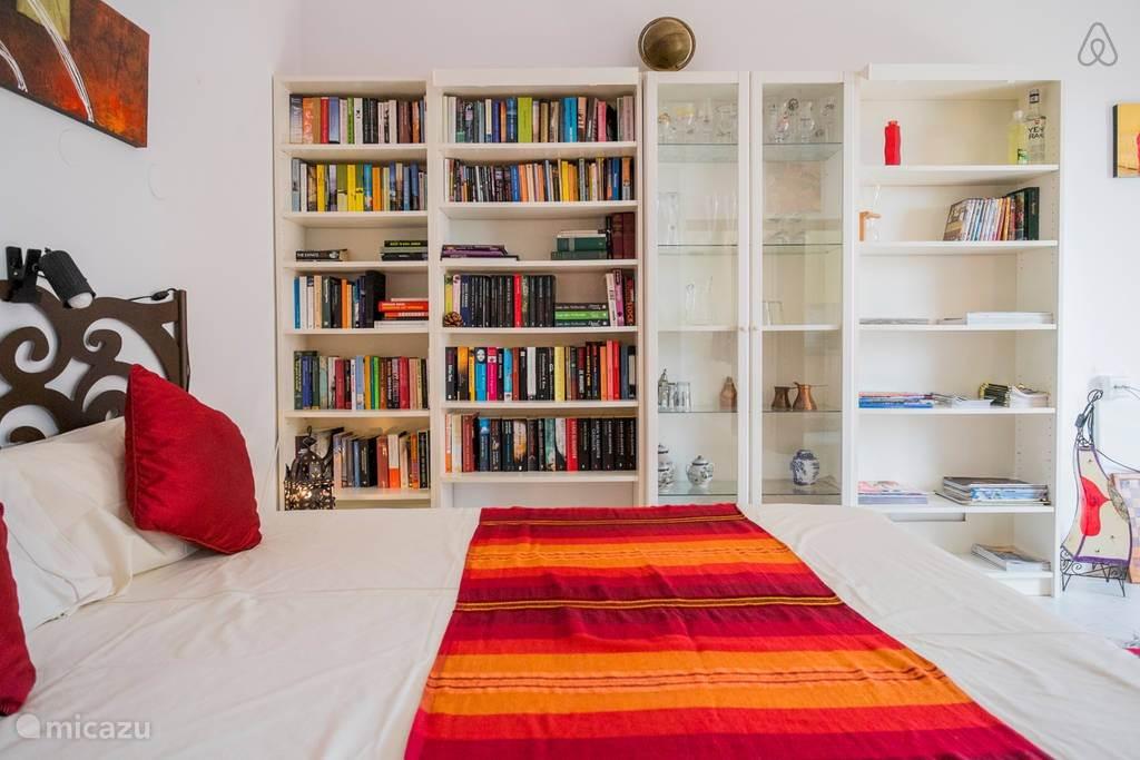 De woon/slaapkamer heeft een boekenkast met veel recente boeken in alle genres.