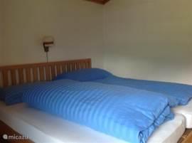 Een fijne slaapkamer met balkon aan de zonzijde en een extra bed in een aansluitende, afzonderlijke ruimte. Ideaal met kleine kinderen. Hier kan eventueel nog een extra bed voor een kind worden bijgeplaatst.