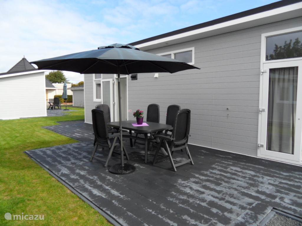 Op het terras van de Rialto staat een comfortabel tuinset met verstelbare stoelen. De parasol hoort daar ook bij.
