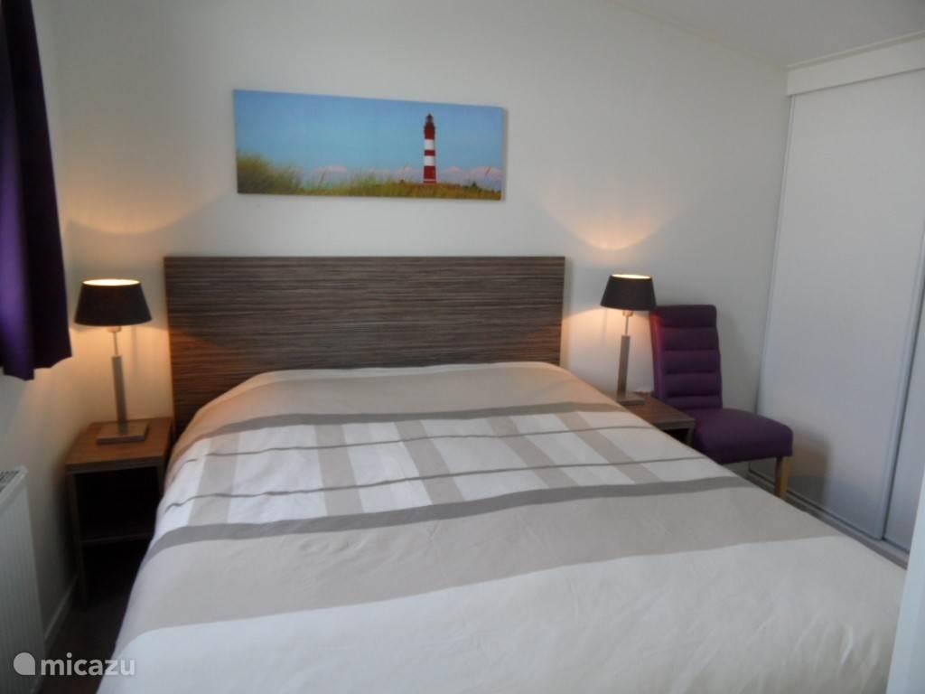Ruime slaapkamer met tweepersoons bed, draai kiepraam, kapstok, nachtkastjes met bedlampjes. Ruime hang legkast met schuifdeur