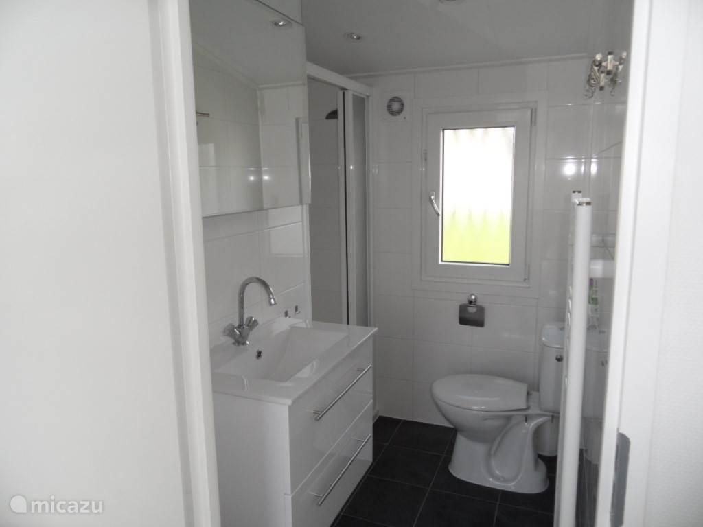 De badkamer is voorzien van een douche, draai kiepraam, verwarming en toiletkast met wastafel met laden. Toilet en ruim voldoende mogelijkheden om je handdoeken op te hangen.