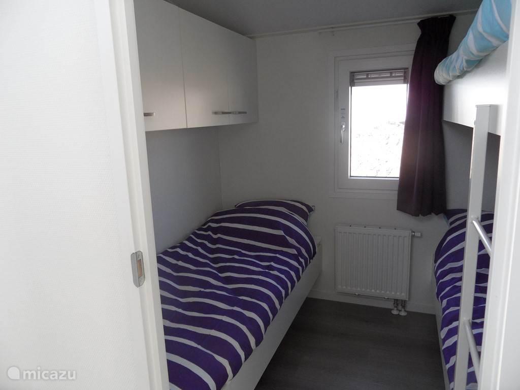 De kleine slaapkamer hier in spiegelbeeld. Heeft 1 persoonsbed en 1 stapelbed. Tevens nachtkastje (niet op foto afgebeeld). Ook hier kunt je voldoende ventileren door het draai kiepraam. Boven het 1 persoonsbed is een kastruimte.