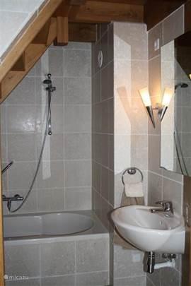 In de badkamer is een bad, douche en wastafel aanwezig.