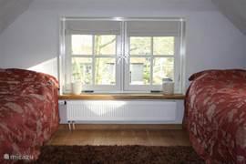 De tweede slaapkamer heeft twee eenpersoonsbedden die opgemaakt zijn bij aankomst.
