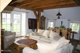 De landelijk ingerichte woonkamer met grote zithoek rondom de (electrische) openhaard en uitkijkend op de tuin met terras is genieten!