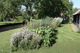De fraai aangelegde ruime tuin met planten, groot grasveld en grenzend aan het water