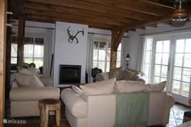 De gezellige woonkamer met zit rondom de (electrische) openhaard. Er is een tv en voldoende licht om een boek te lezen. Mocht u liever buiten willen zitten, via de openslaande deuren komt u op het terras met houten stoelen en tafel uitkijkend over de tuin, water en de Weerribben-Wieden