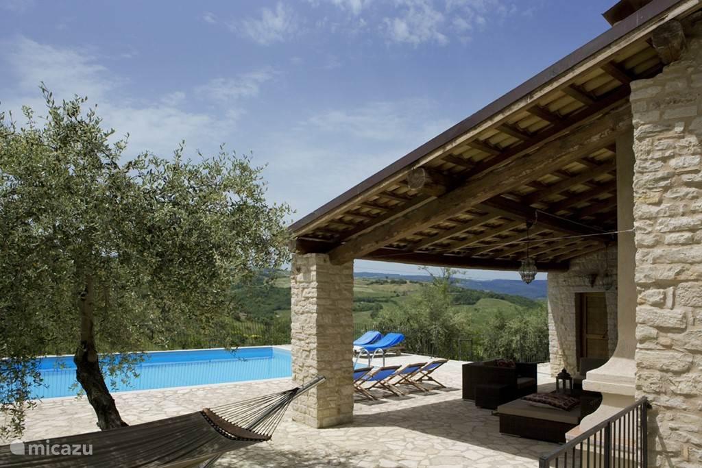 De veranda bij het zwembad biedt een heerlijke schaduwplek met panoramisch uitzicht