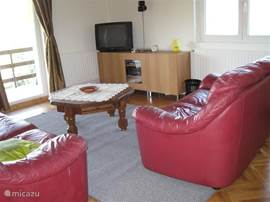 Living room with 2 seater sofa and a 3 seater sofa. Links with glass front Duer to the balcony.