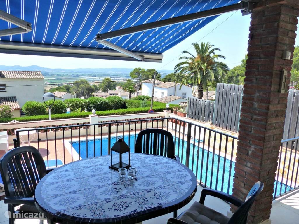 Tuinset op het overdekte terras, met zicht op het zwembad en de vallei/ zee