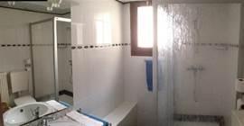De badkamer op de bovenverdieping met douche, wastafel met kastruimte en toilet