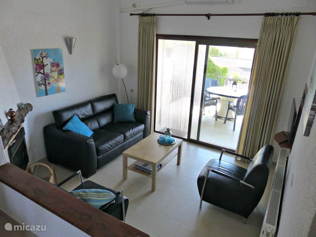 Gezellige woonkamer met eet- en zithoek en toegang tot overdekt terras via schuifpui