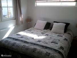De slaapkamer met 2 persoonsbed en grote kledingkast