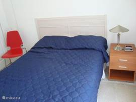 Slaapkamer met 2 persoon bed, inbouw kasten en zicht op terras/zwembad