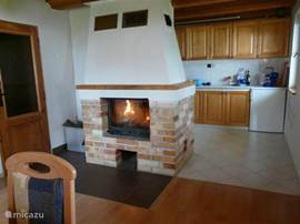 Fireplace in the living room with open kitchen.