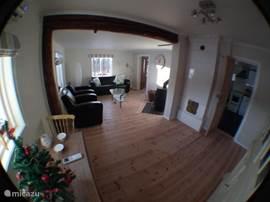 De huiskamer met houtkachel.