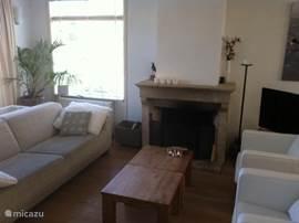Zitgedeelte van de woonkamer met openhaard, televisie, boekenkast