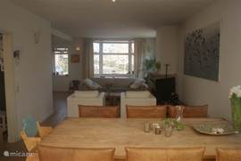 Eetkamer gedeelte van de woonkamer met 6 comfortabele leren eetkamerstoelen en een kinderstoel