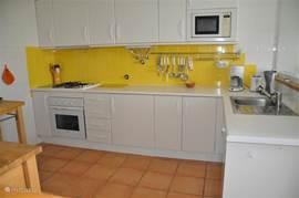 Ruime keuken voorzien van 4-pitsgaskomfoor, vaatwasser, oven, magnetron en ijskast met vriezer.