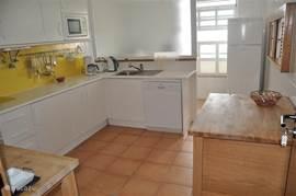 Achter de keuken een wasruimte met wasmachine en droger.