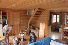 De woonkamer, in vol bedrijf.... open toegang naar keuken, trap naar de slaapverdieping. Volop ruimte voor 6 personen.