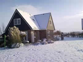 Aanzicht van het huis en de tuin in de winter.