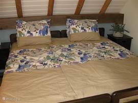 Slaapkamer Zuid. Met lits-jumeaux bed inclusief bedlinnen. Let op de authentieke details in het dak/plafond.