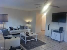 Leuke moderne woonkamer met makkelijk te reinigen tegelvloer ivm zand (strand om de hoek). Grote LED televisie, natuurlijk gratis WIFI, leren banken, airconditioning en plafond ventilator