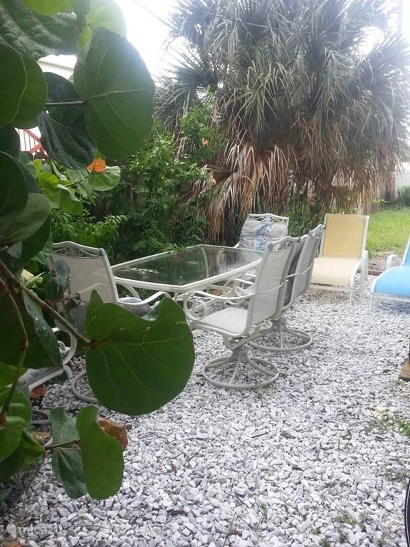 Een klein achtertuintje met barbecue, eettafel en stoelen
