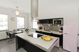 hoogglans zwarte keuken met rvs schouw voorzien van alle apparatuur + kookeiland met 2 barkrukken en alle gemakken die een keuken hebben moet; tevens mogelijkheid gebruik laptop aan het kookeiland