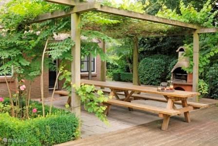 Een van de terrassen met grote tafel en bbq/buitenhaard
