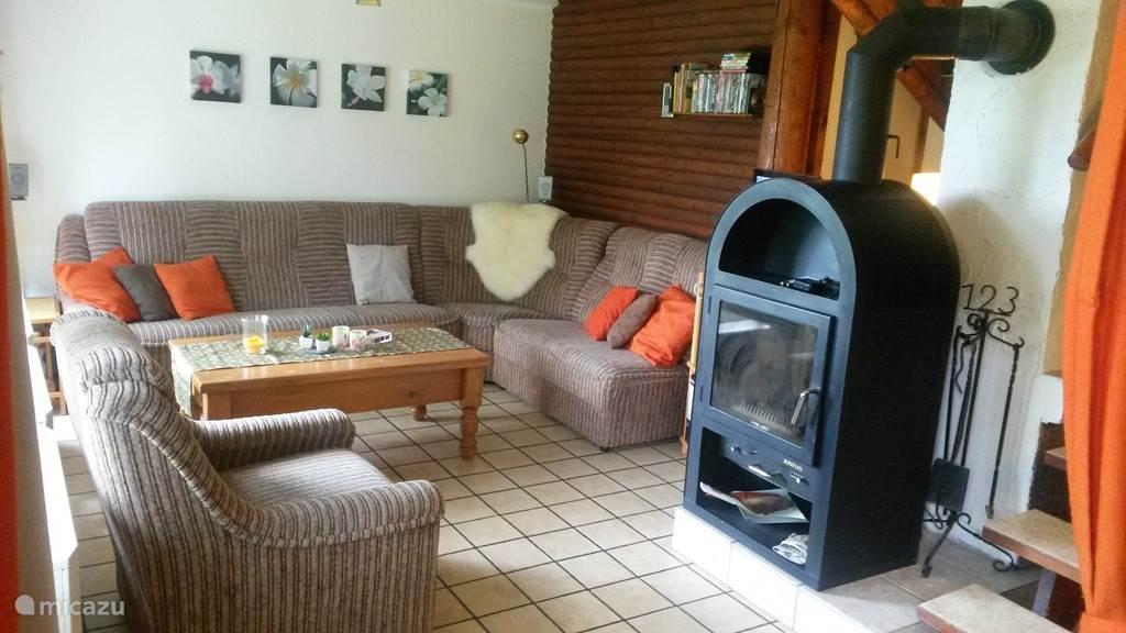 In de woonkamer staat een ruime hoekbank, die heerlijk zit. In de losse fauteuil zit u heerlijk vlak voor de houtkachel en de TV.