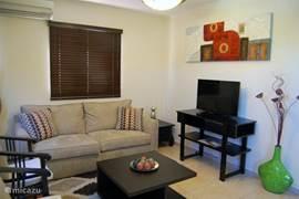 Das Wohnzimmer mit zwei ausklappbaren Doppeldiwanbett und Kabel-TV mit drei niederländischen Kanälen. Das gesamte Haus verfügt über eine Klimaanlage.