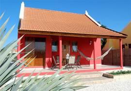 De achterkant van de woning, met porch en hangmat om heerlijk weg te dromen. Ruime tuin om rustig van de zon te genieten. Aan de linkerkant is het washok met wasmachine en droger te zien.