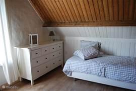 In deze slaapkamer staan aan deze zijde, een één-persoons bed en kast..