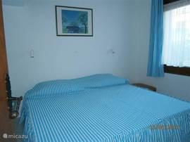 2e slaapkamer met 2 bedden en uitzicht op de tuin
