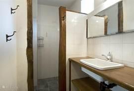 De oude houten elementen geven deze badkamer een rustieke uitstraling.