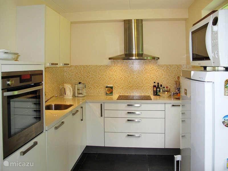 De keuken is voorzien van alle apparatuur, en staat via een ronde poort in open verbinding met de woonkamer.