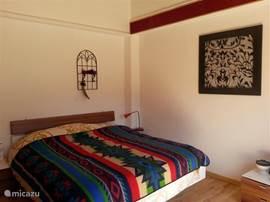 Royaal 2 persoonsbed in de sfeervolle slaapkamer op de 1e verdieping met veel privacy. Openslaande deuren naar een terrasje.