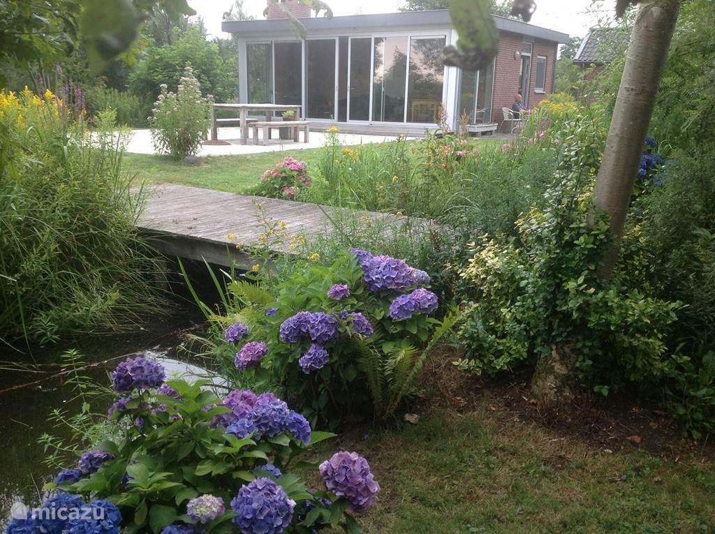 Ons vakantiehuisje in de zomer, gezien vanaf het bruggetje, het grote terras heeft een buiten-eettafel .........