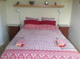 Slaapkamer met open inloopbadkamer. In de woonkamer staat een sofa, die als 2 persoons slaapbank gebruikt kan worden