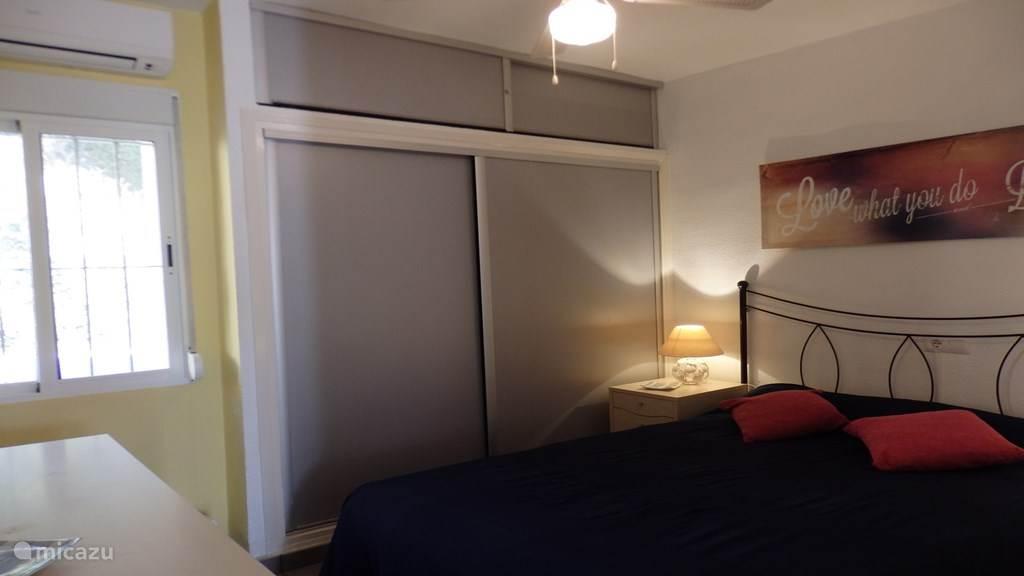 Hoofdslaapkamer met 2-persoonsbed, plafondventilator en airco