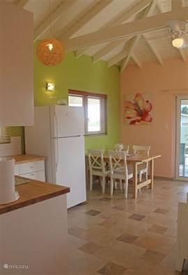 Doorkijk van de hal naar de keuken en woonkamer met eethoek, appartement #1
